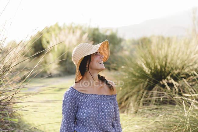 Fröhliche junge Frau schaut weg, während sie einen Sonnenhut auf dem Land trägt — Stockfoto