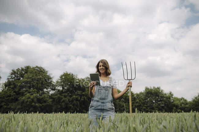 Jovem com garfo de feno e tablet em pé em um campo de grãos no campo — Fotografia de Stock