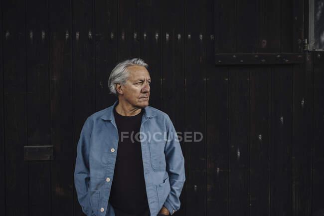 Homem sênior em pé na parede de madeira olhando para os lados — Fotografia de Stock