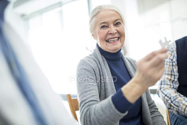 Сміється з старшої жінки, яка тримає п'єсу на пенсії — стокове фото