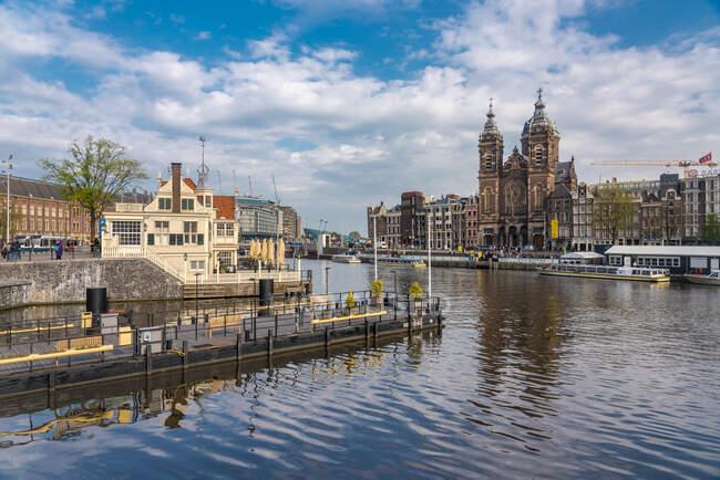 Países Bajos, Holanda Septentrional, Amsterdam, Canal de la ciudad con la Basílica de San Nicolás en el fondo - foto de stock