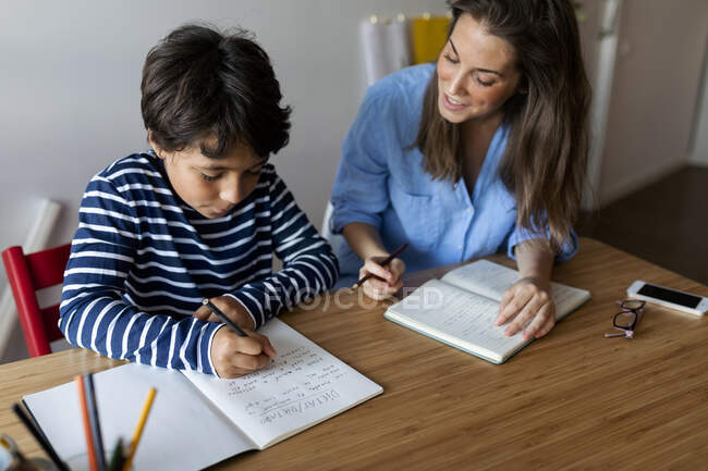 Young woman assisting boy in writing homework on table at home — Stock Photo