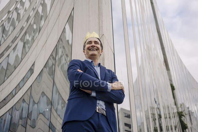 Щасливий дорослий бізнесмен, який носить в місті іграшкову корону. — стокове фото
