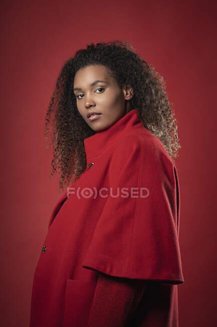 Серйозна молода жінка з кучерявим волоссям на червоному фоні. — стокове фото