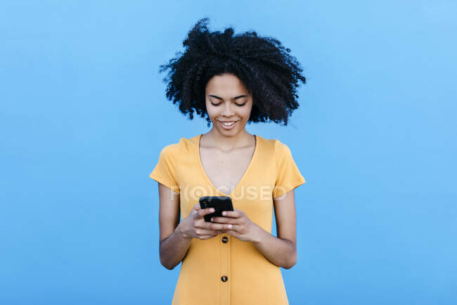 Smiling young woman using smart phone while standing against blue wall — Stock Photo