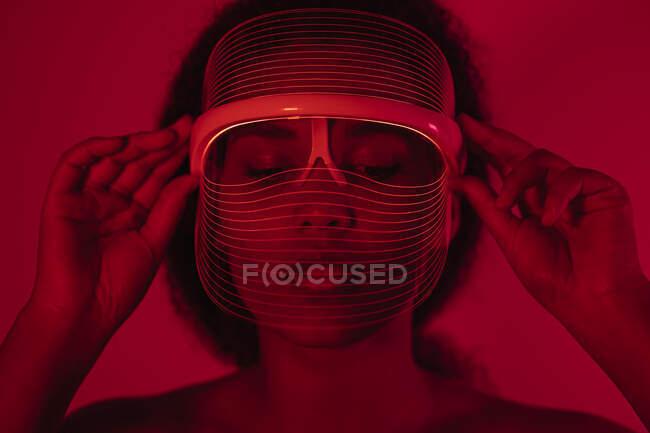 Primer plano de la mujer joven con máscara led roja contra la pared en casa - foto de stock