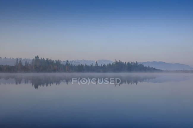Bella alba sul lago nella nebbia — Foto stock
