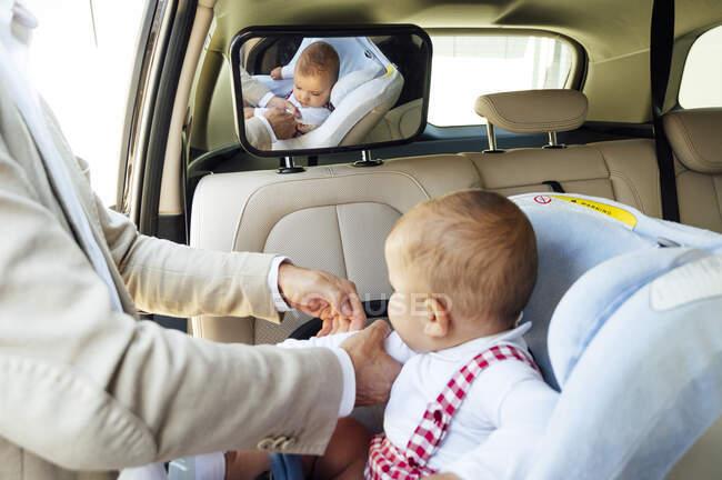 Батько сидить на дитячому сидінні в машині. — стокове фото