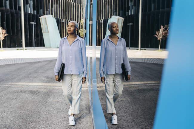 Empresária desviando o olhar enquanto caminhava na cidade — Fotografia de Stock