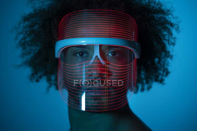 Primer plano del hombre con máscara led roja contra la pared en casa - foto de stock