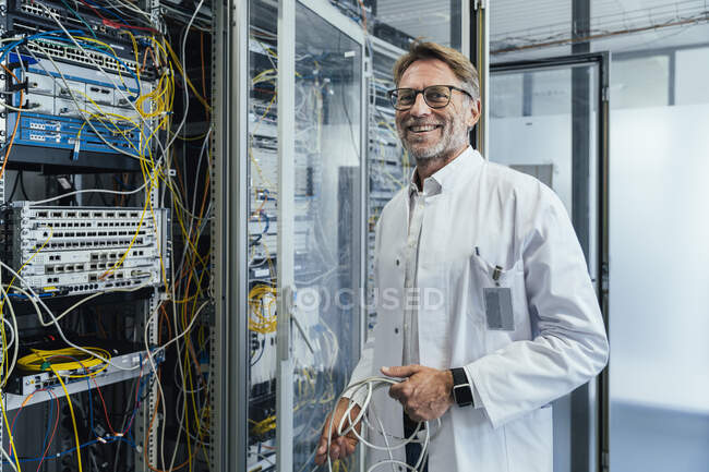 Male IT professional holding cables standing by network server in date center - foto de stock