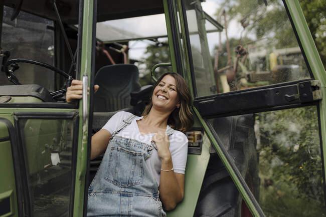 Jovem alegre em um trator no campo — Fotografia de Stock