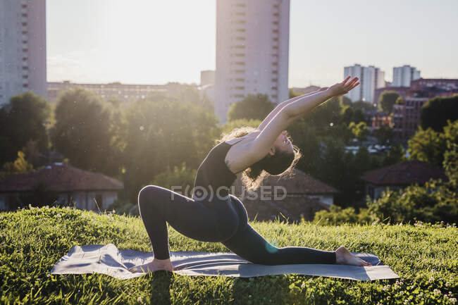 Young woman practicing yoga in warrior position at city park during sunny day — стоковое фото