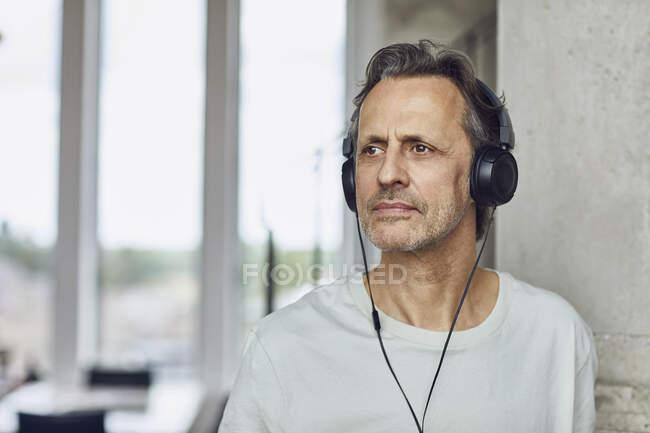 Senior man with headphones listening music in a loft flat — Stock Photo