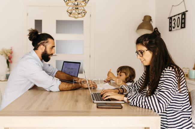 Жінка працює над ноутбуком, а батько з донькою малюють на обідньому столі вдома. — стокове фото