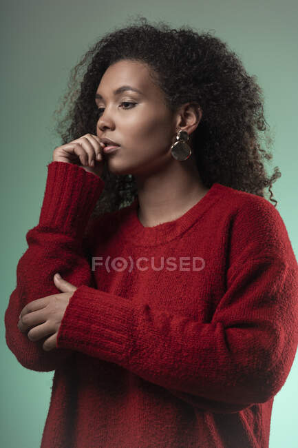 Nachdenkliche junge Frau mit lockigem Haar vor blauem Hintergrund — Stockfoto