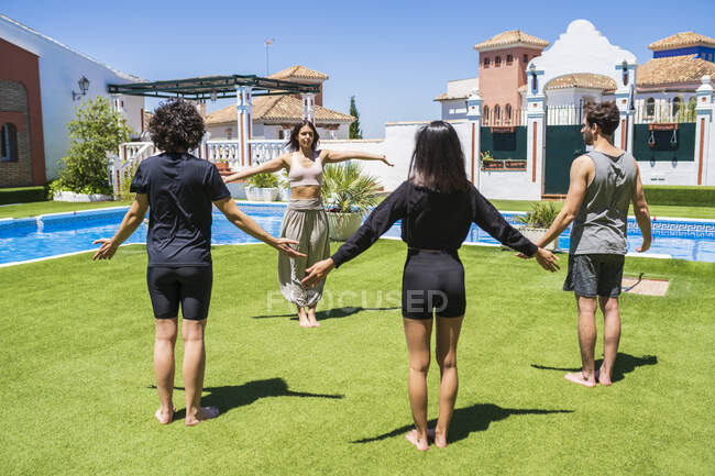 Young woman teaching yoga to friends at back yard on sunny day — Stock Photo