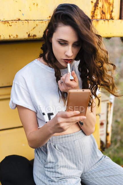 Mulher bonita aplicando batom enquanto sentado na plataforma metálica — Fotografia de Stock