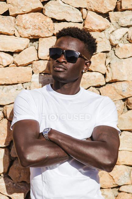 Gros plan d'un jeune homme portant des lunettes de soleil les bras croisés contre un mur de pierre — Photo de stock