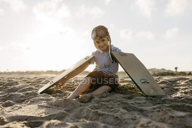 Niño con alas de avión y gorra sentado en la arena en la playa - foto de stock