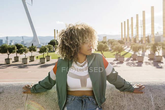 Mujer de moda reflexiva apoyada en muro de contención en la ciudad - foto de stock