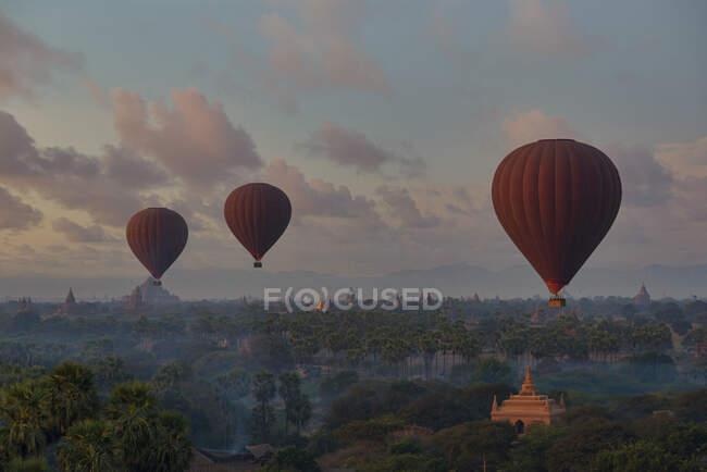 Myanmar,Mandalay Region,Bagan, Hot air balloons flying over Buddhist temples at dawn — Stock Photo