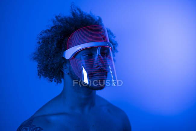 Primer plano del joven sin camisa con máscara led roja contra la pared en casa - foto de stock