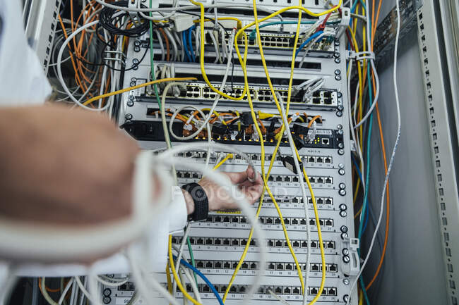 Close-up of mature man hand plugging cable in data center rack — Stock Photo