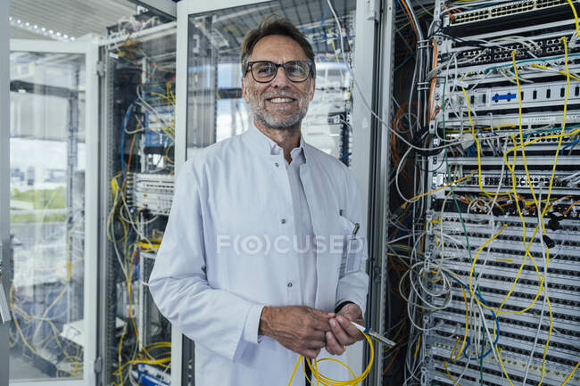 Male IT professional holding cables looking away while standing in server room — Stockfoto