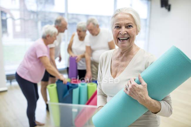 Счастливая старшая женщина держит коврик для йоги после занятий — стоковое фото
