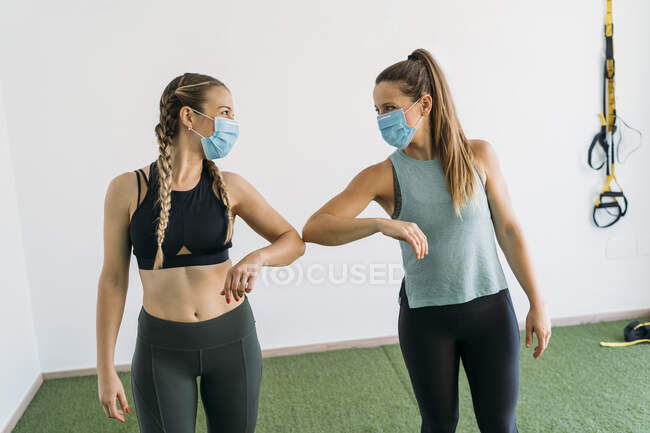 Two sporty women wearing face masks giving elbow bump at health club — Fotografia de Stock