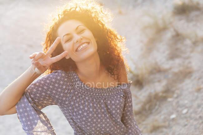 Joven alegre mostrando señal de paz durante el día soleado - foto de stock