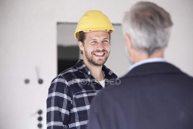 Trabalhador da construção sorrindo usando chapéu duro conversando com arquiteto na construção de casa — Fotografia de Stock