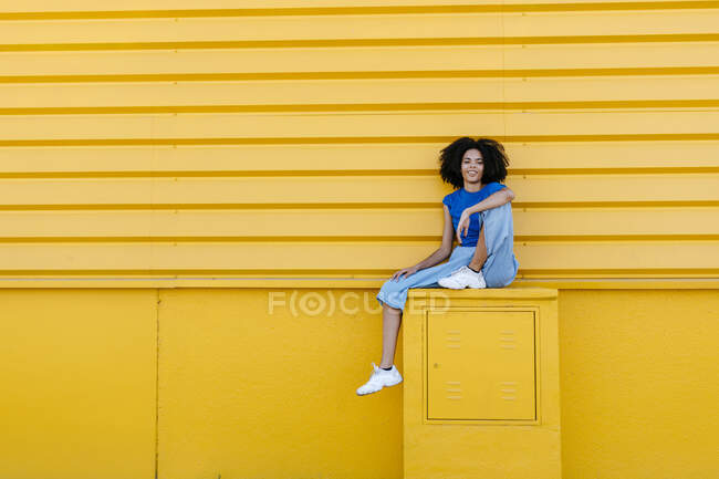 Pretty woman sitting on platform in front of yellow wall, smiling — стокове фото