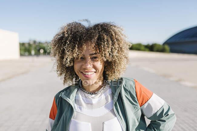 Mujer joven y segura con el pelo rizado durante el día soleado - foto de stock