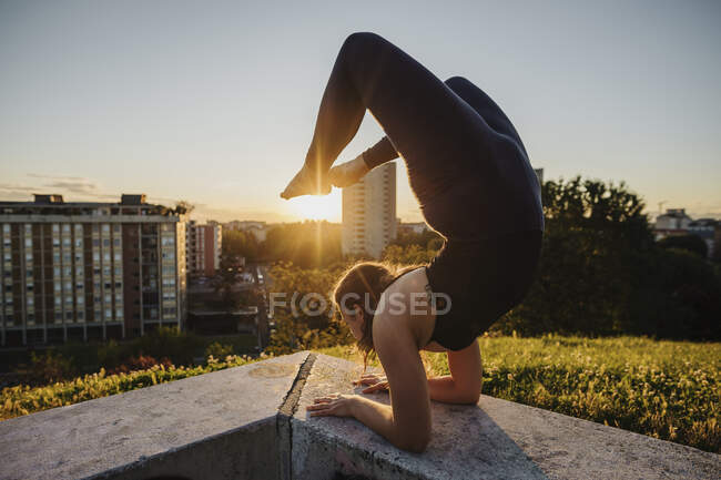 Flexible young woman performing yoga on retaining wall in city during sunset — стоковое фото