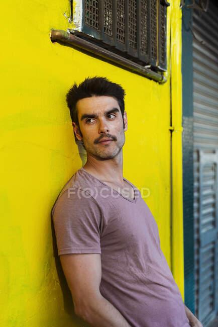 Pensativo hombre guapo mirando hacia otro lado mientras se apoya en la pared amarilla de la ciudad - foto de stock