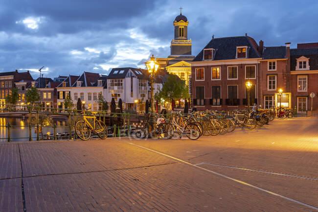 Paesi Bassi, Olanda Meridionale, Leida, Biciclette parcheggiate lungo la vecchia strada illuminata al tramonto — Foto stock