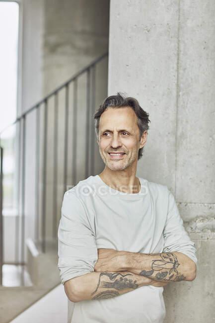 Smiling tattooed senior man in a loft flat — Stock Photo