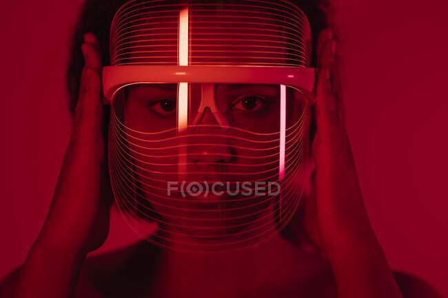Primer plano de la mujer que usa máscara de terapia de luz roja contra la pared en casa - foto de stock