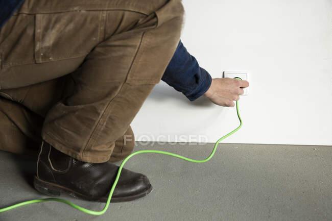 Gros plan du technicien insérant la prise de courant à la maison de construction — Photo de stock