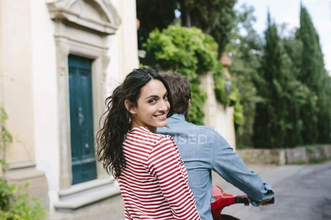 Усміхнена жінка сидить з хлопцем на Веспі. — стокове фото