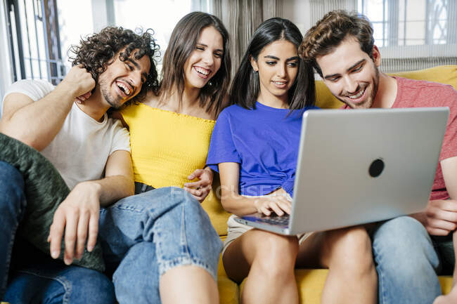 Happy multi-ethnic friends sharing laptop while sitting in living room — Stock Photo