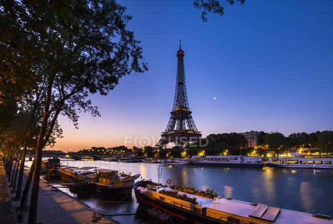 Ейфелева вежа біля річки Сена проти ясного блакитного неба при заході сонця, Париж, Франція. — стокове фото