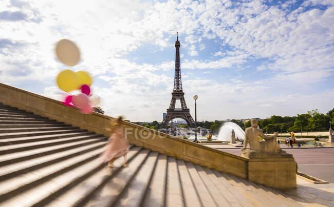 Donna con palloncini che scende dalle scale contro la Torre Eiffel a Parigi, Francia — Foto stock