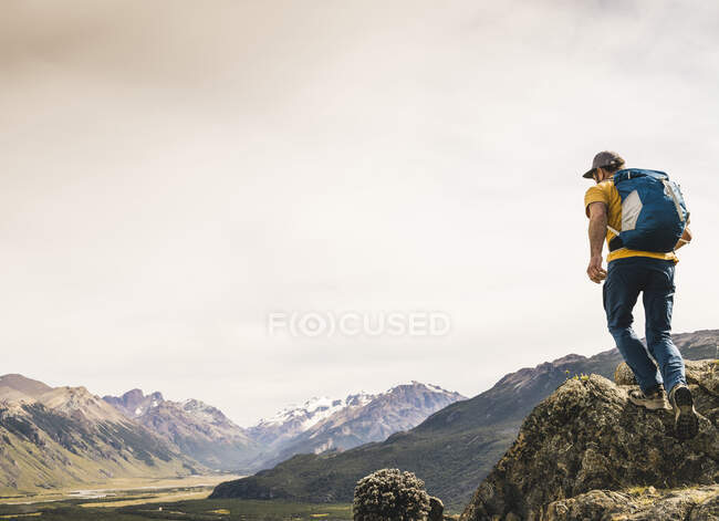 Mature hiker with backpack walking on rock against sky, Patagonia, Argentina — Stock Photo