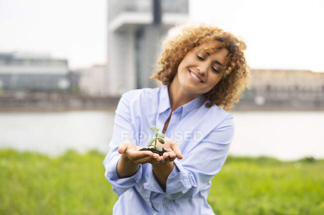 Smiling businesswoman with curly hair holding small plant while standing against sky in city — Fotografia de Stock