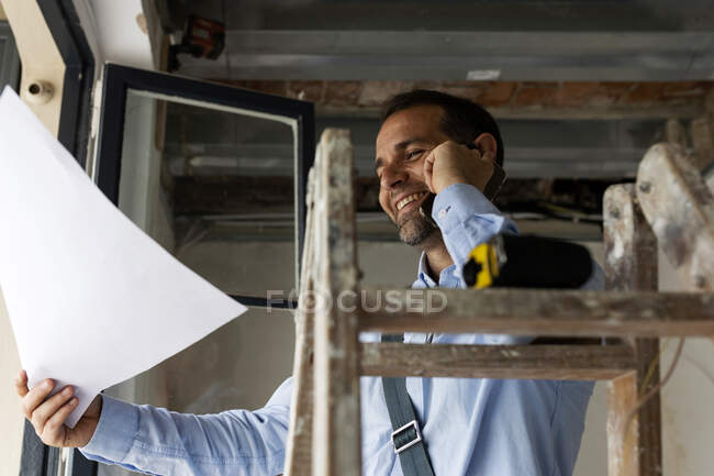 Smiling architect with plan on the phone in a house under construction — Stock Photo