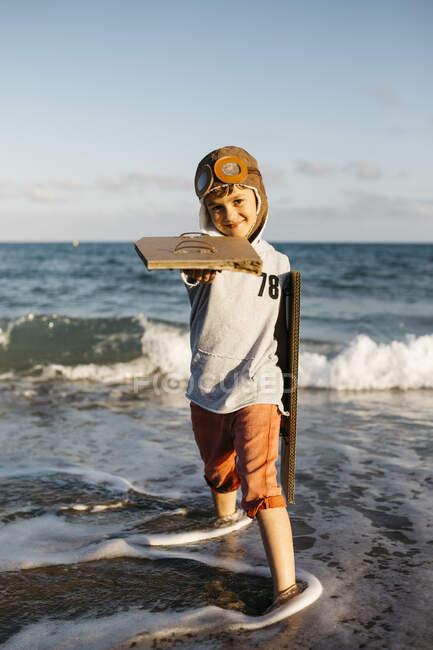 Мальчик с крышкой летчика, держащий картонные крылья, стоя на пляже — стоковое фото