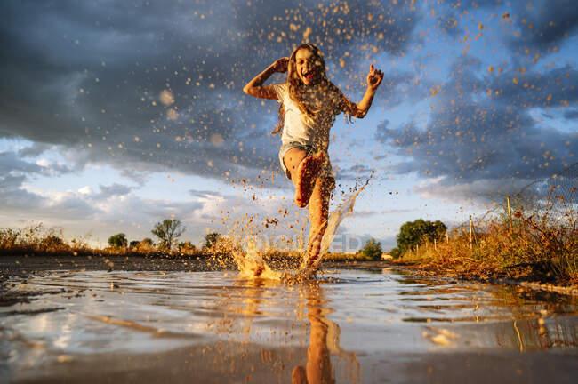 Ragazza felice giocando mentre schizza acqua sulla pozzanghera contro cielo nuvoloso — Foto stock